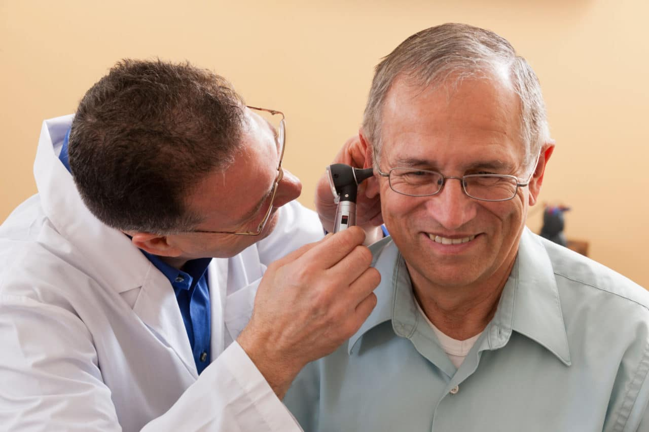A provider inspecting a patient with an otoscope