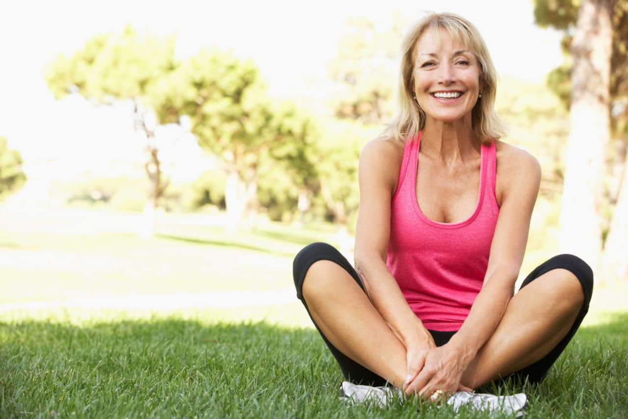 Photo of a woman smiling and sitting cross-legged on a lawn