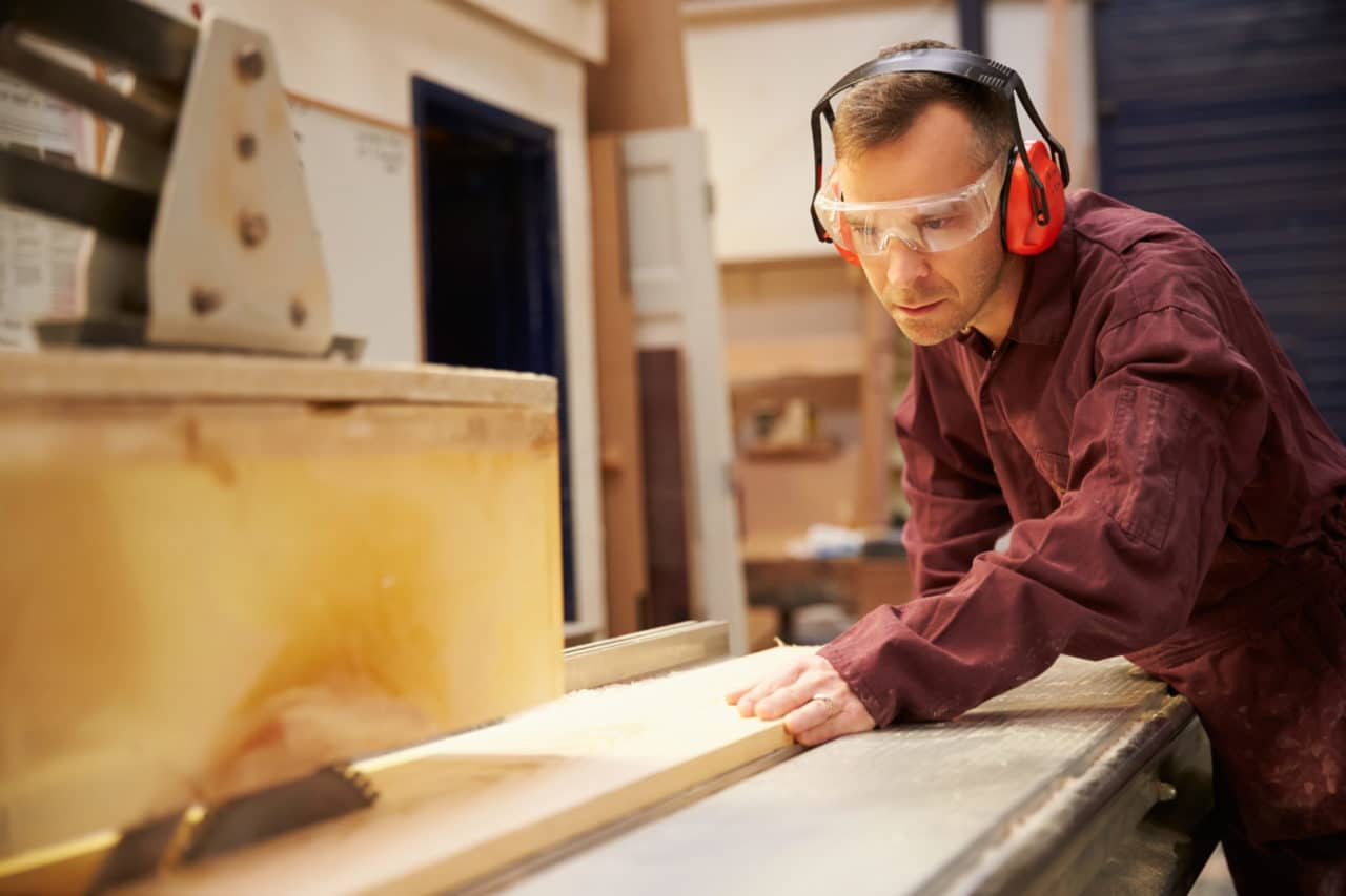 Photo of a person wearing protective headphones while doing woodwork with power tools