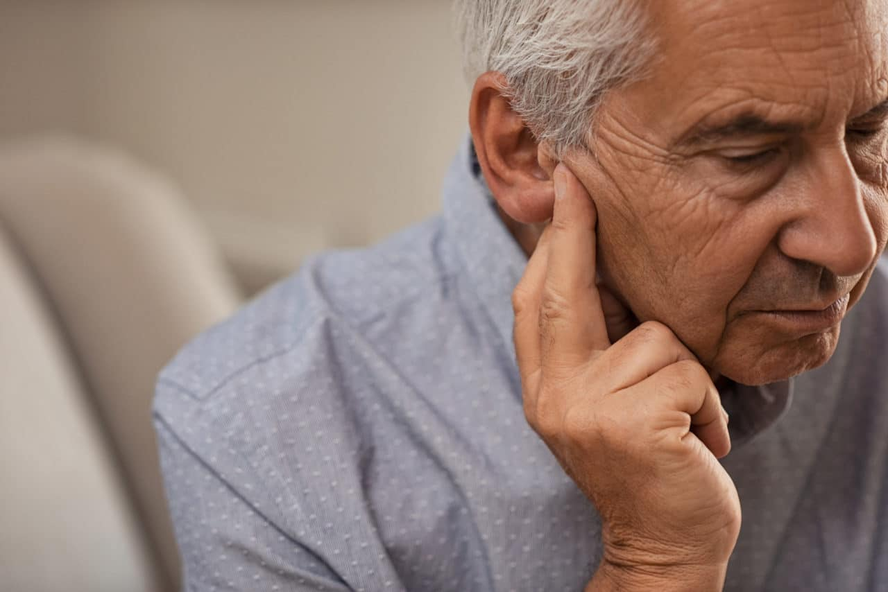 Photo of a man touching his ear with a worried expression