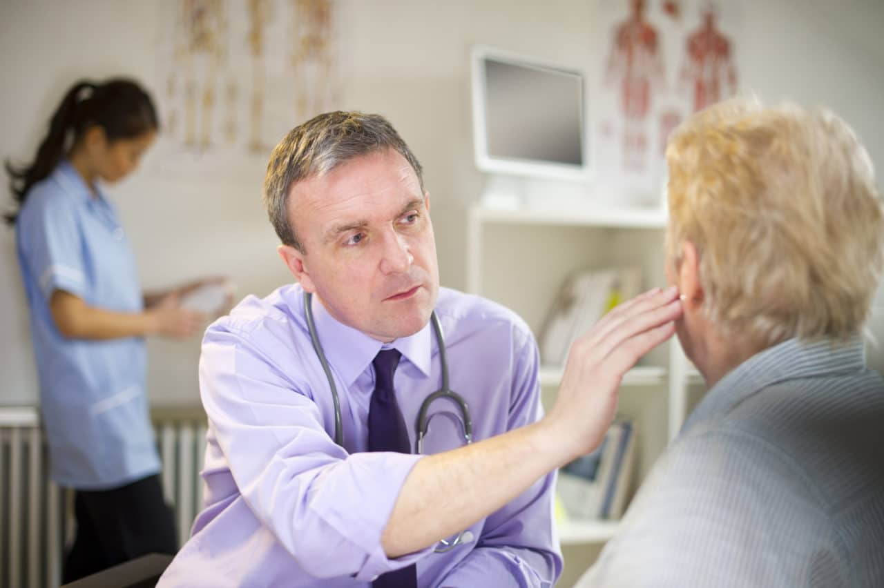 Photo of a provider touching a patient's ear