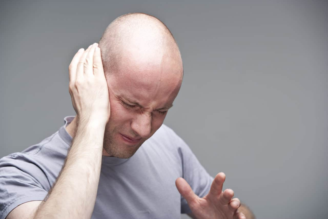 Photo of a person holding one hand up to their ear and wincing in pain