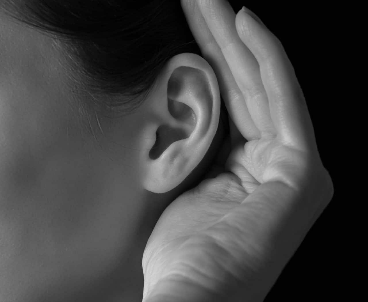 A person cupping a hand around their ear