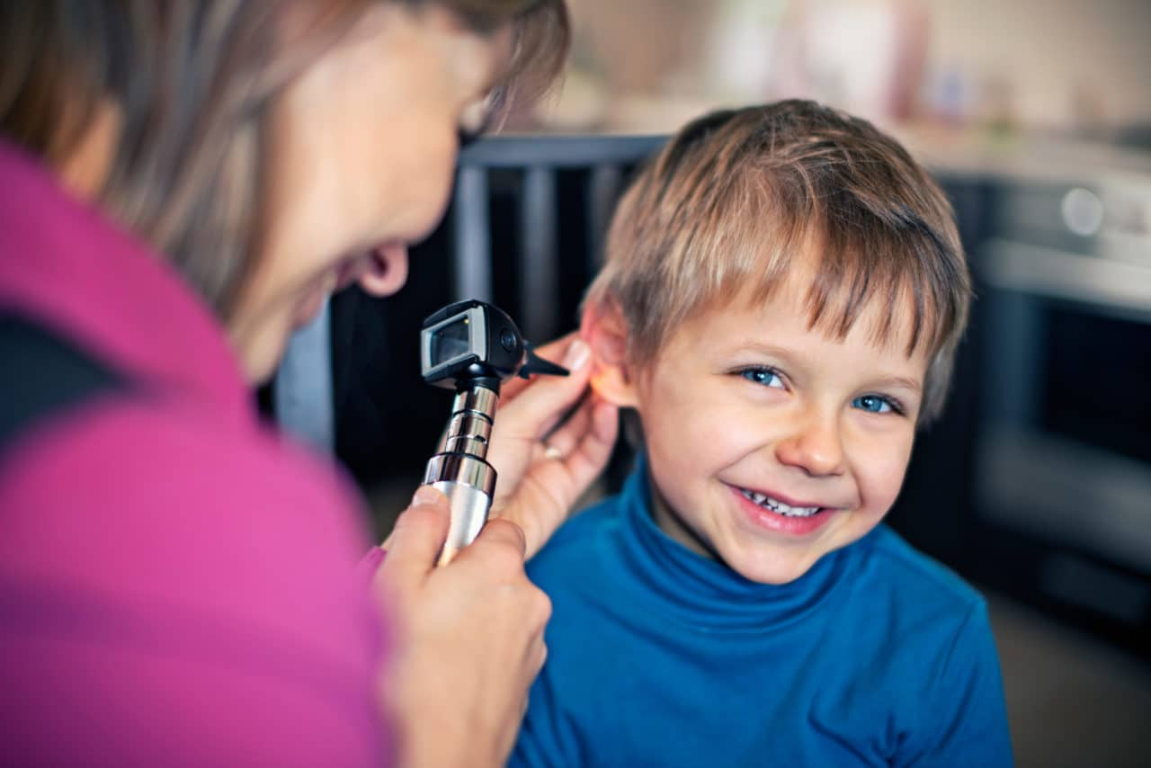 A provider examining a child with an otoscope