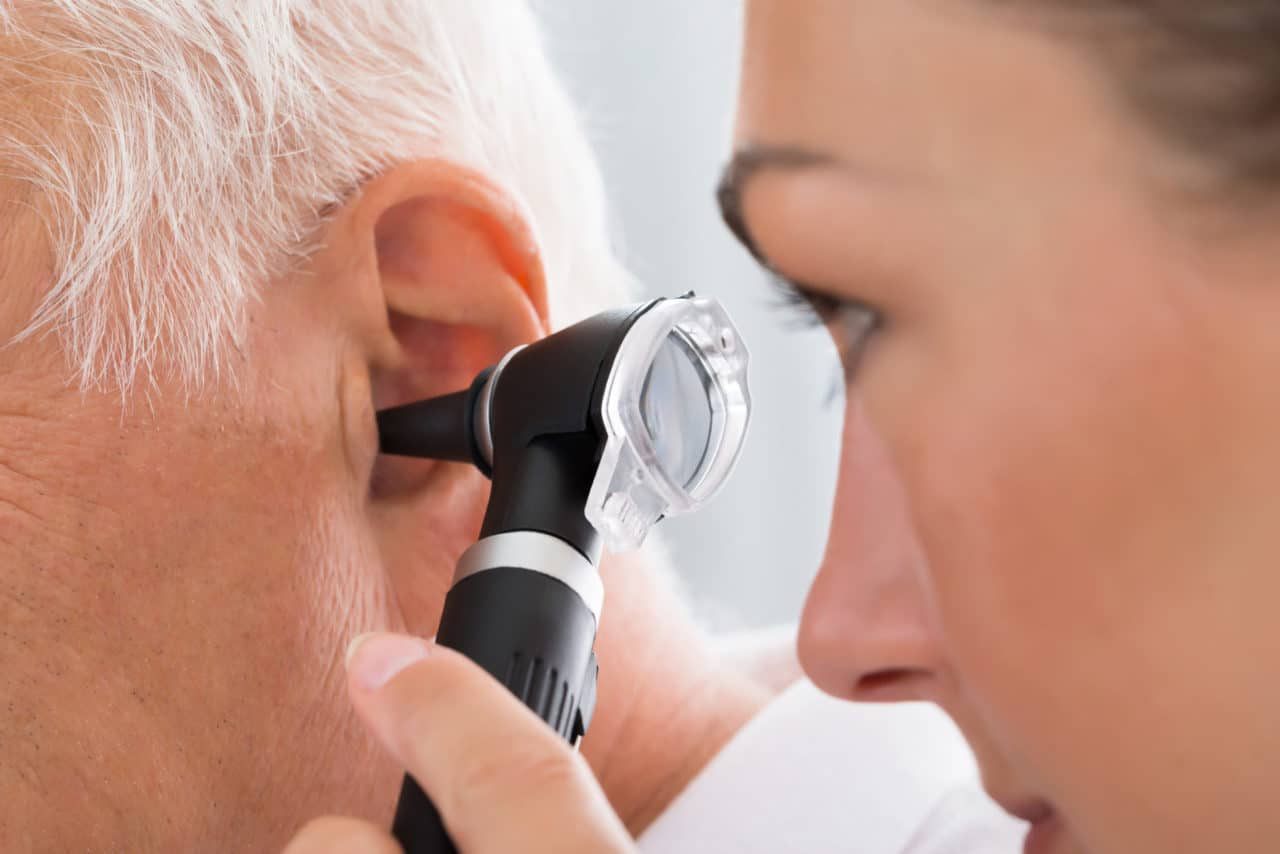 Photo of an audiologist using an otoscope