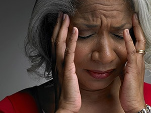 Photo of a person holding their head in both hands and wincing in pain
