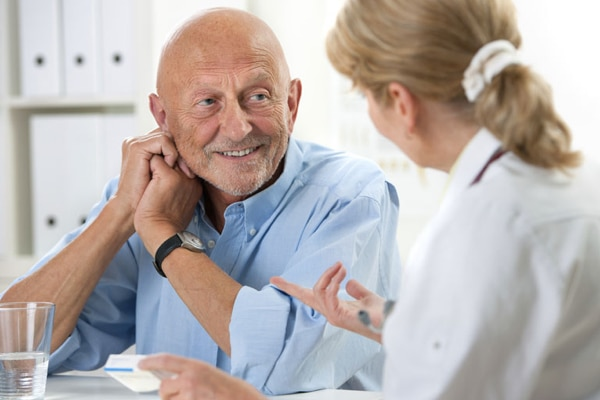 A patient smiling while listening to a provider explain the options