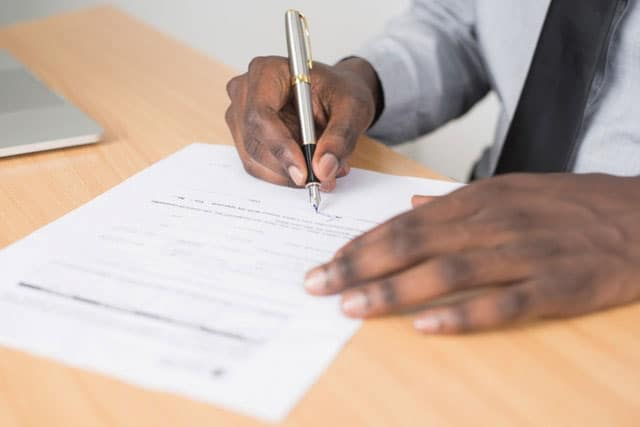 Photo of a person signing a filled-out form