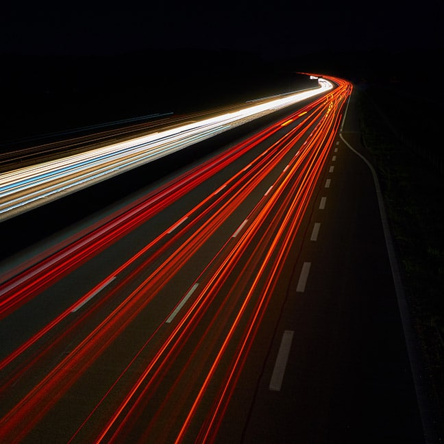 A long-exposure photo of car lights streaming through the night