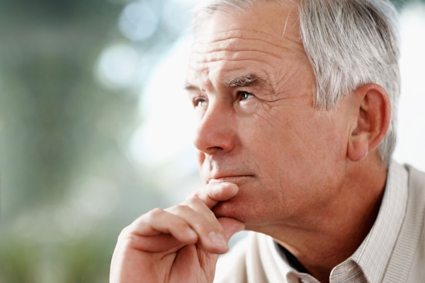 Photo of an elderly man holding his chin looking thoughtful