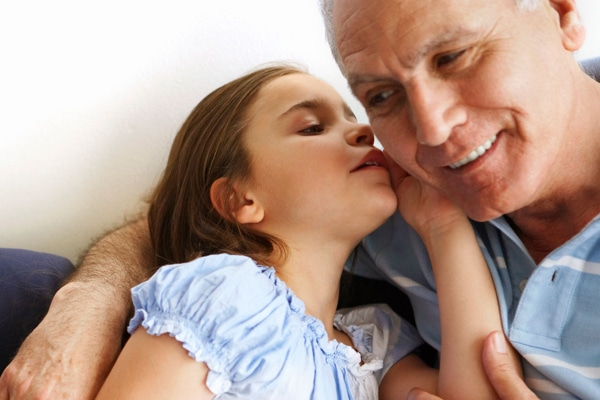 A child whispering into an older person's ear