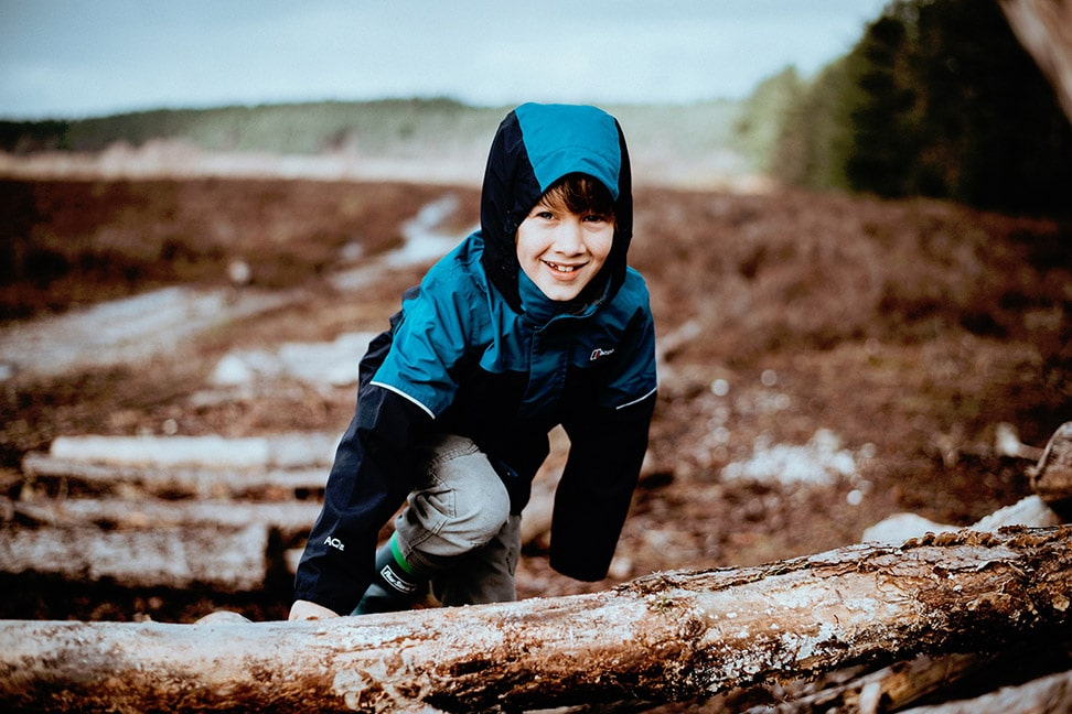 Photo of a boy wearing a jacket and climbing a pile of logs