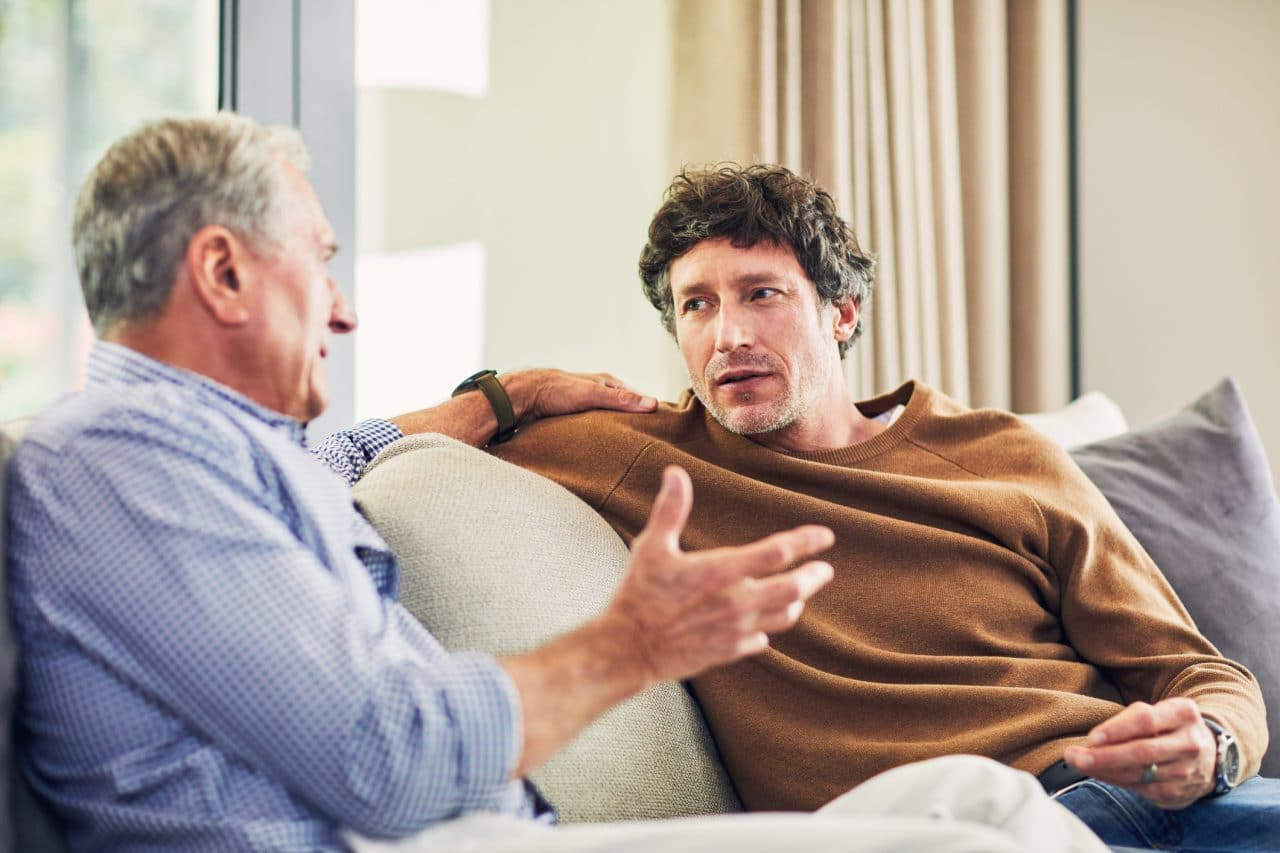 Younger man and older man talking on a couch