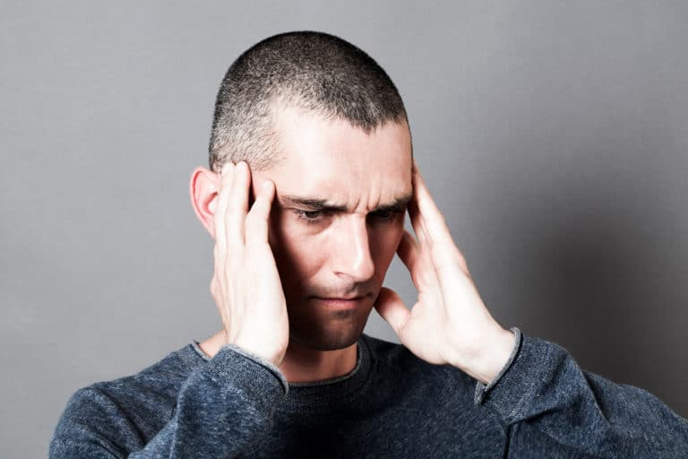 man holding his head in pain