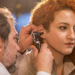 An Audiologist doing a hearing exam on a female patient
