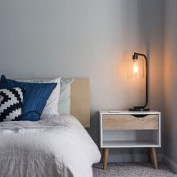 A bed and nightstand with a light.
